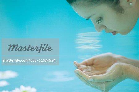 Jeune femme se penchant sur l'eau, ventouses mains, gros plan