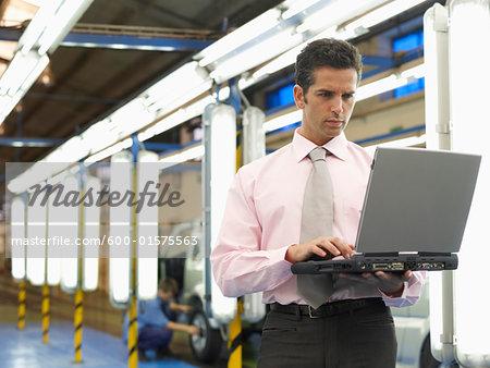 Man Using Laptop in Automotive Plant