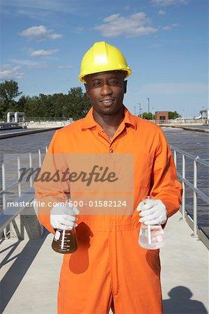 Homme avec des échantillons d'eau à la station d'épuration