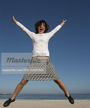 Femme sautant à la plage