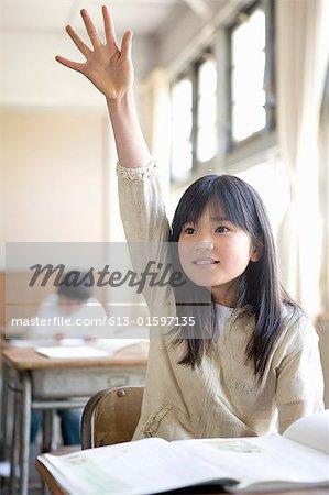 Girl (6-7) raising hand in school classroom