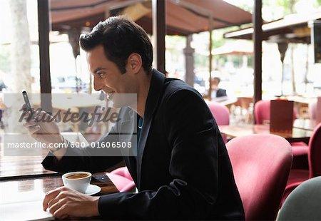 Mann mit Handy im Cafe