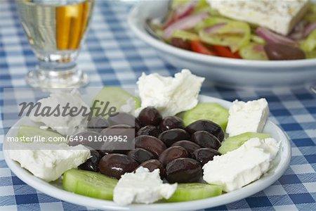 Plateau à olives feta et du concombre Salade grecque table et retsina en arrière-plan.