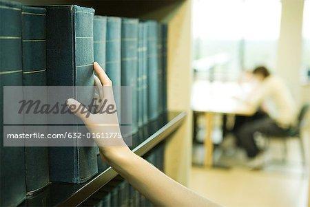 Ouvrage de référence étudiante prise d'étagère de bibliothèque