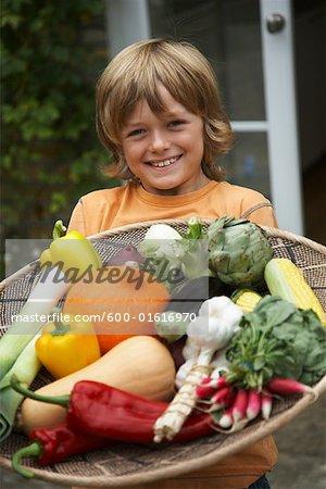 Junge hält Tablett mit Gemüse