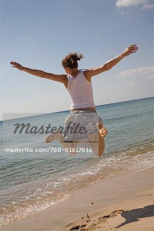 Femme sautant en l'Air sur la plage, Sardaigne, Italie