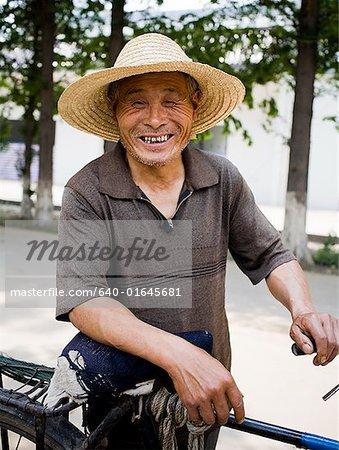 Homme d'âge mûr avec chapeau de paille à l'extérieur avec le sourire de bicyclette