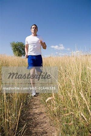 Homme Jogging dans le champ