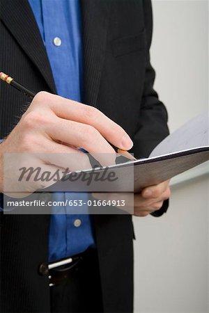 Businessman writing in a personal organizer