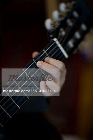 Détail d'un jeune garçon jouant une guitare acoustique