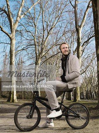 Un homme portant vos écouteurs et assis sur un BMX dans un parc