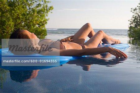 Femme flottant sur matelas pneumatique