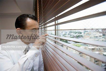 A businessman looking through window blinds