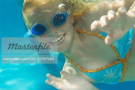 Girl wearing swim goggles underwater
