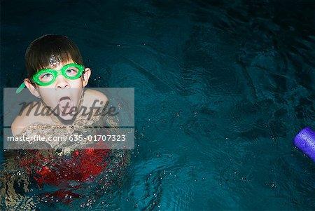 Boy wearing swim goggles in swimming pool