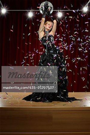 Frau auf der Bühne mit Mikrofon mit Konfetti geworfen an Ihr