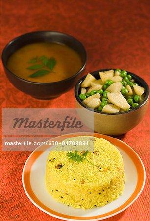Nahaufnahme der Reis auf einem Teller mit Linsen und Pees mit Kartoffel-Scheiben