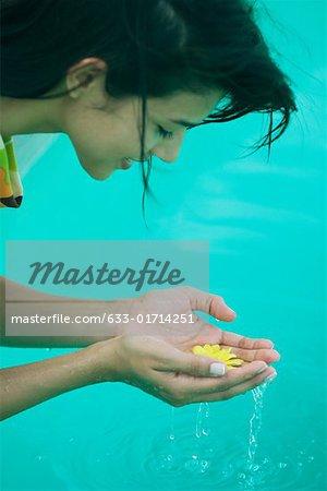 Jeune femme à se pencher sur la piscine et fleur de tenue dans les mains, recadrée vue latérale