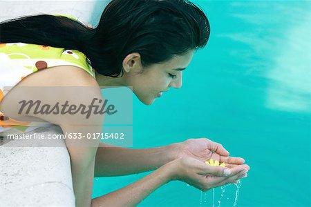 Jeune femme de se pencher sur le bord de l'eau, ramasser des fleurs dans les mains