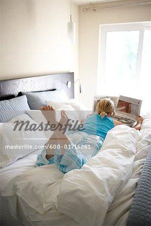 Femme au lit, en lisant le journal