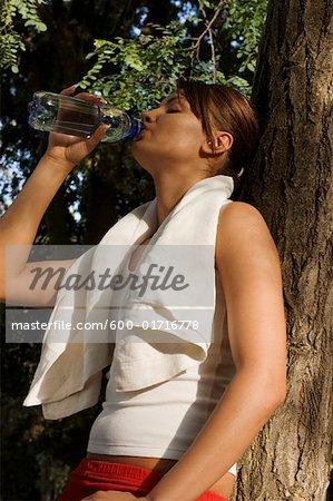 Frau trinkt aus Flasche Wasser