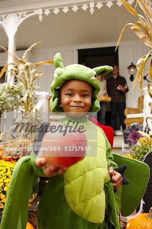 Porträt von Boy Holding Apple und Süßes oder Saures zu Halloween