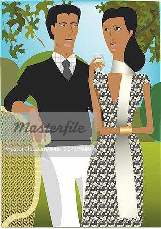 Couple bien habillés, boire un verre dans le jardin