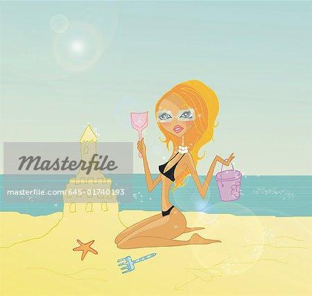 Blonde sur la plage de construire un château de sable