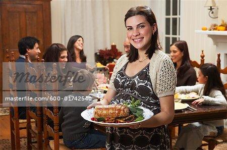 Femme avec de la nourriture pour le dîner de famille