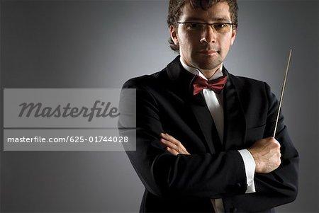 Gros plan d'un musicien tenant le bâton de chef d'orchestre