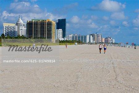Tourists walking on the beach, South Beach, Miami Beach, Florida USA