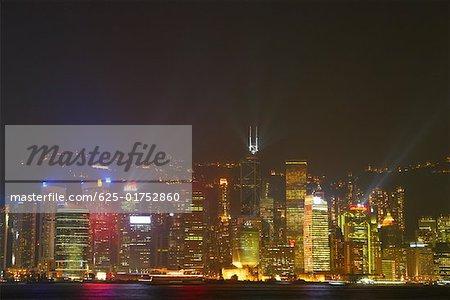 Skyscrapers lit up at night in a city, Victoria Harbor, Hong Kong Island, Hong Kong, China