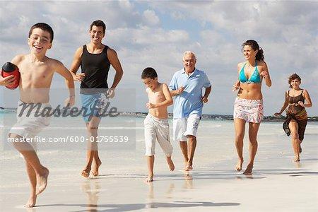Famille jouant au Football sur la plage