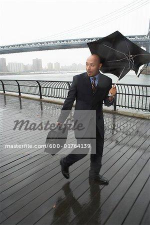 Gens d'affaires marchant sous la pluie par le pont de Brooklyn, New York City, New York, États-Unis