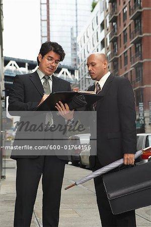 Les hommes d'affaires sur le trottoir en regardant les fichiers, New York City, New York, États-Unis