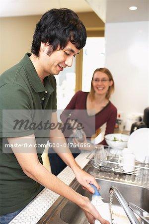 Homme et femme, laver la vaisselle