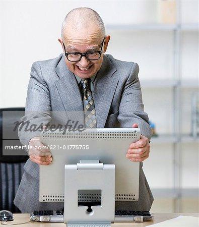 Angry senior man grabbing computer