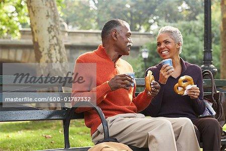 Paar mit Kaffee und Brezeln in Park City, New York City, New York, Vereinigte Staaten