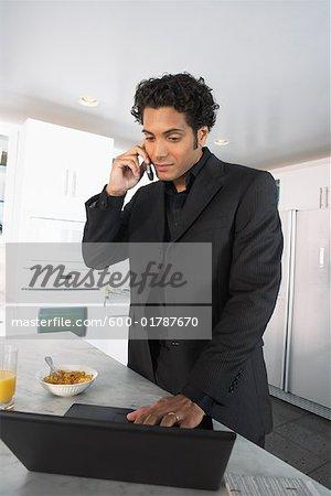 Homme d'affaires à la maison, ordinateur portable à l'aide et parlait au téléphone cellulaire