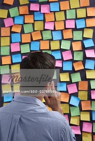 Man Looking at Self-Adhesive Notes