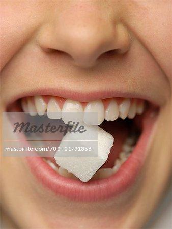 Gros plan de la bouche de la femme, tenant le morceau de sucre entre les dents