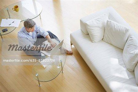 Homme dans le salon, assis sur le plancher à l'aide d'ordinateur portable