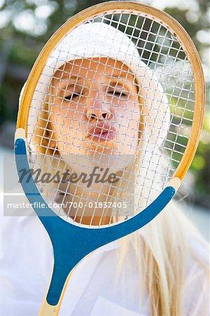 Frau Blasen Küsse durch Tennisschläger