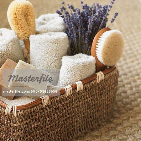 Nature morte de panier avec serviettes, savon, brosses et lavande
