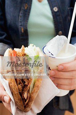Mains tenant un döner kebab et l'yaourt à boire