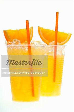 Orangensaft mit crushed-Eis, orange Keile und Stroh