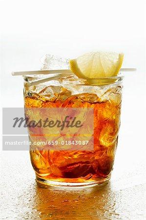 Eistee im Glas mit Keil von Zitrone und Strohhalme