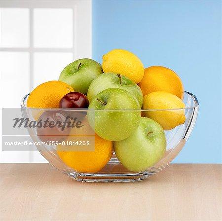 Fruits frais dans un bol de verre devant la fenêtre