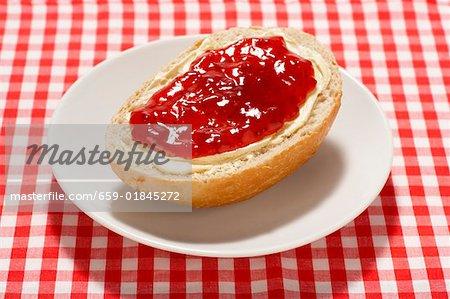 Brötchen mit Butter und Erdbeermarmelade