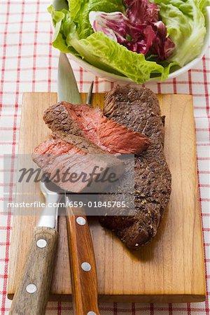 Beef steaks, partly sliced, salad